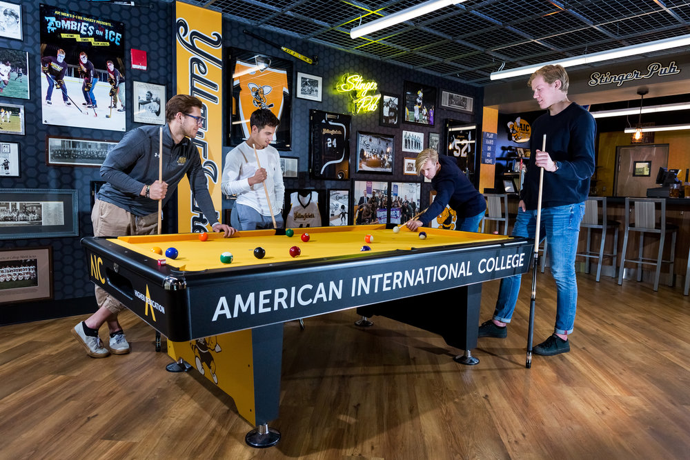 students playing pool on a table that says American International College