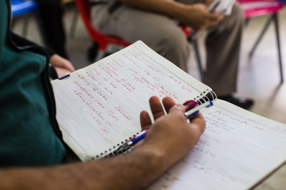 An Iraqi man takes notes during English classes at Collateral Repair Project's community center in Amman, Jordan.