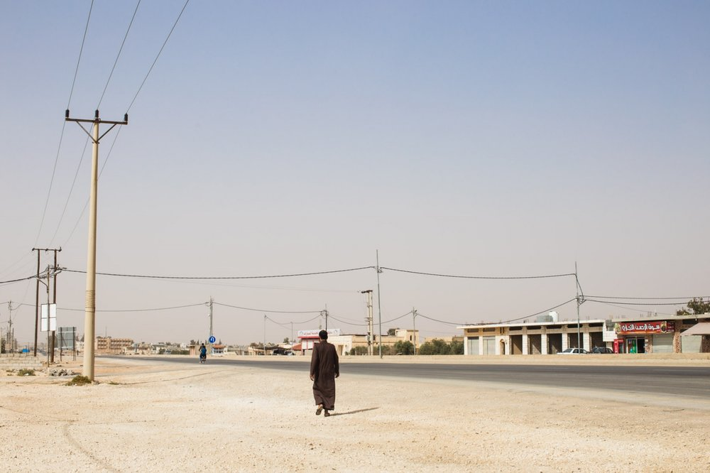 A man walks along the desert stretch of road outside of Za'atari Refugee Camp in northern Jordan.