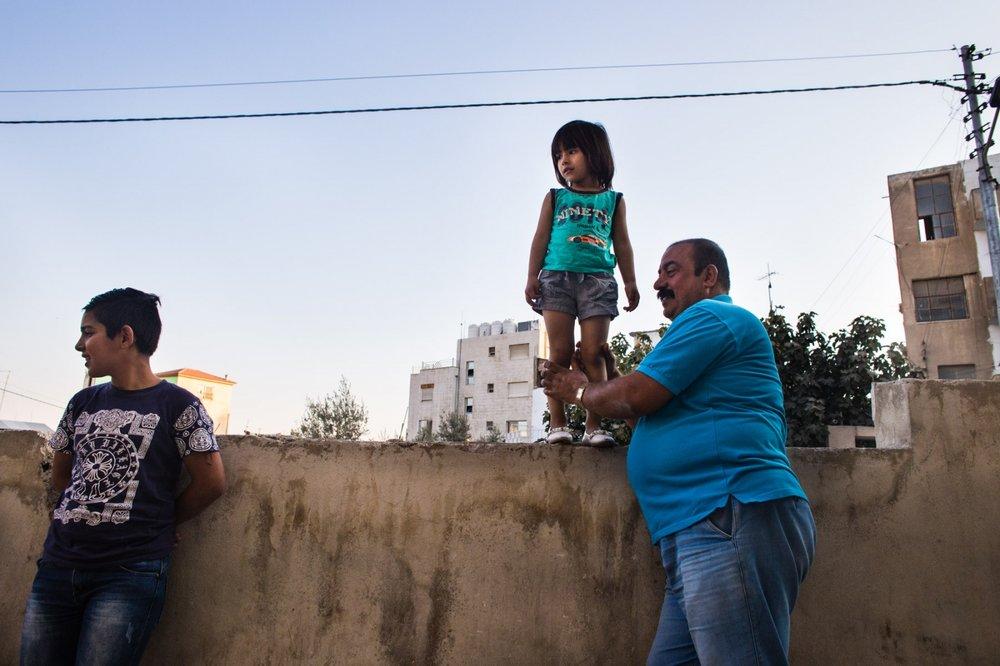 An Iraqi Kurdish man holds his daughter, Mariam, up on the wall after picking her up from an after school program. His family has been in Jordan for several years and were waiting on a visa to the US.