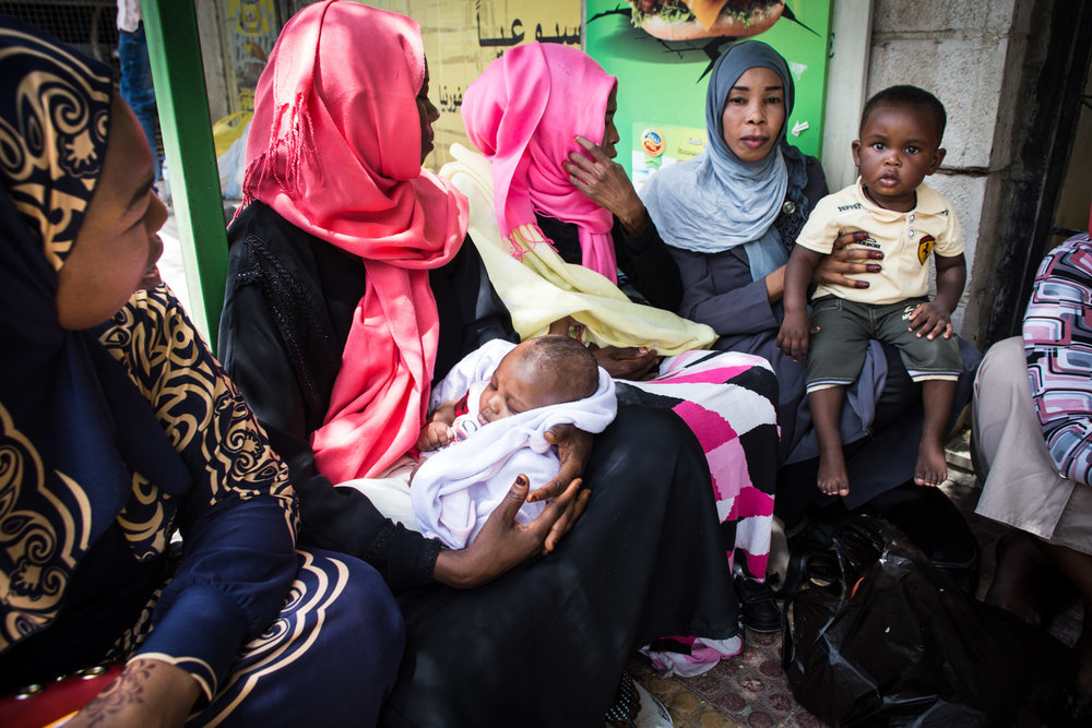 Sudanese women sit with their children outside a supermarket in the Jebel Ashrafieh neighborhood of Amman, Jordan, while they wait their turn to use their monthly 25 JD ($35) food voucher to purchase groceries for their families.