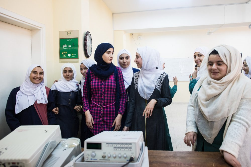 Rand Al-Bustanji (center) visits with her friends in their science classroom. Rand hopes to continue with sports, but also has aspirations of studying computer science in university.
