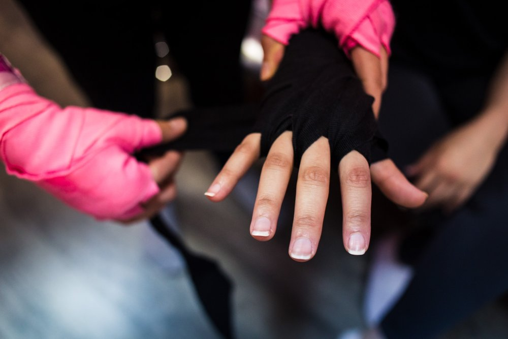Two students help each other wrap their hands before starting their self defense class at She Fighter in Amman, Jordan on August 21, 2015. The She Fighter studio was founded by Lina Khalifeh, and offers self defense classes to young women to protect against harassment.