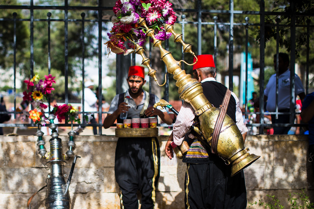 Two men selling iced hibiscus juice rest in the shade. Thousands gathered in Amman, Jordan, to mark the centennial of the Great Arab Revolt on June 3, 2016.