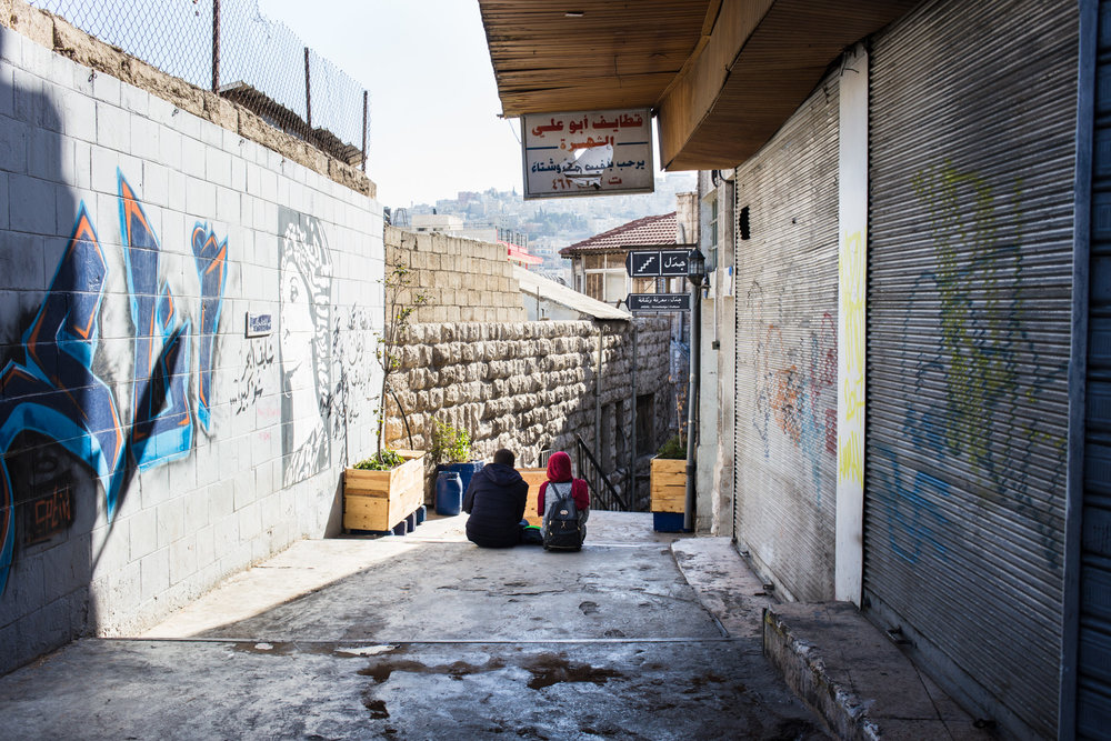 A young man and woman sit together on a staircase leading from the Jebel al-Weibdeh neighborhood to downtown Amman, on December 2, 2017.