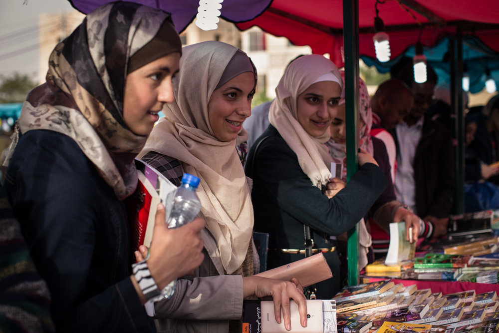 Young women browse the books on display at a literary fair on April 16, 2015 in Amman, Jordan.