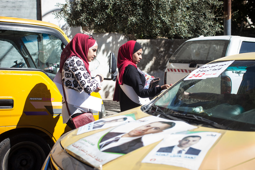 Young Jordanian women hand out campaign materials as voters drive to the polls in Amman, Jordan, during parliamentary elections on Sept. 20, 2016.