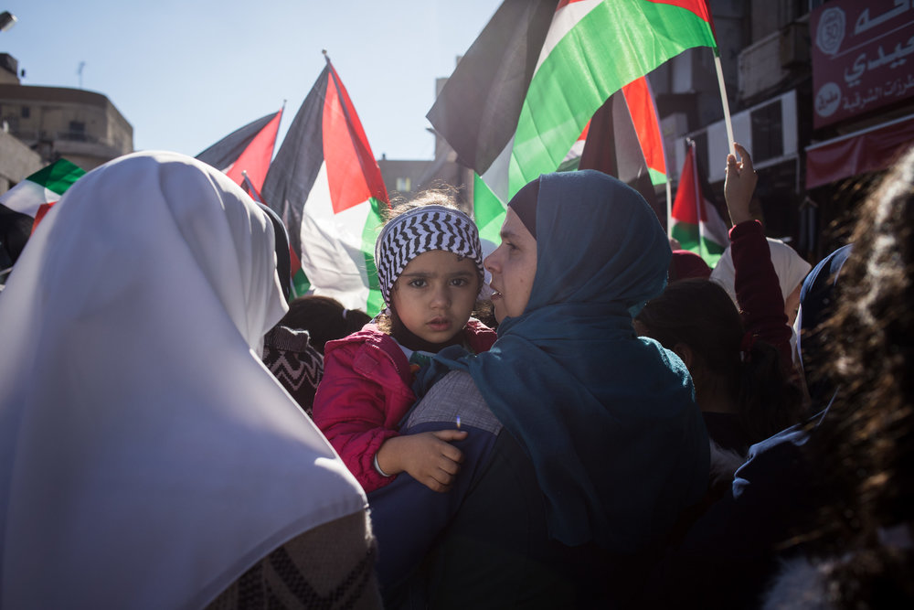 A young girl wearing a Palestinian keffiyah-style headband is carried by her mother during a demonstration in downtown Amman, Jordan, on Dec. 8, 2017. The protests come after US President Donald Trump's announcement that the US embassy to Israel would move from Tel Aviv to Jerusalem.