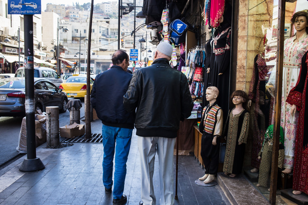 Two elderly men walk arm in arm past shops in downtown Amman on Dec. 2, 2017. Jordan's announcement of plans to build a shiny new city in the desert has been met with criticism, as Amman struggles with rising cost of living, pollution, and lack of public transportation. (AP Photo/Lindsey Leger)