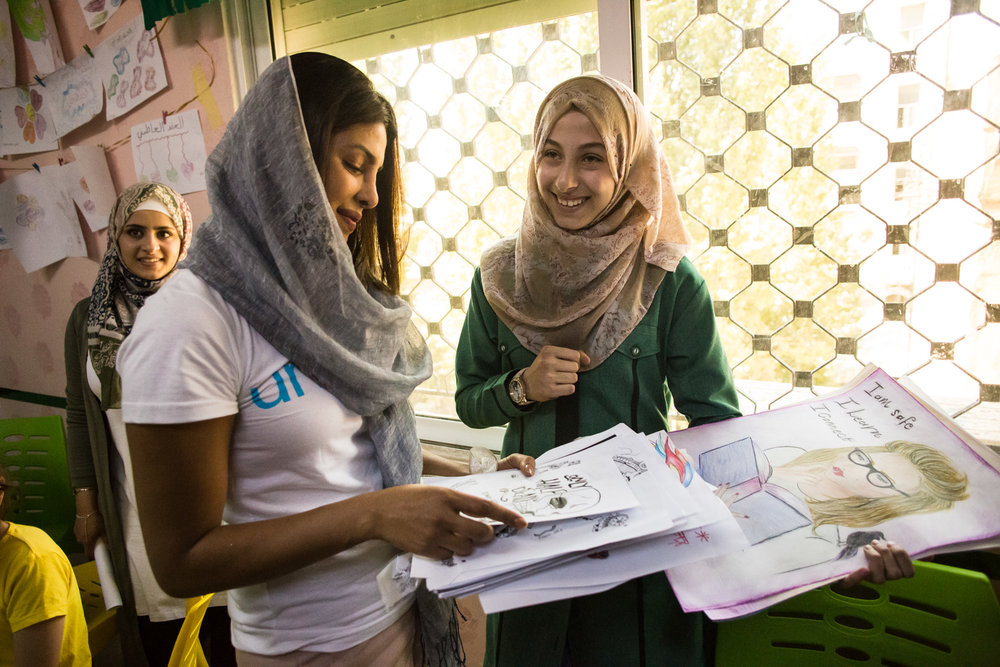Priyanka Chopra, a UNICEF Goodwill Ambassador, views artwork by Eman Ahmad (right), 15, from Aleppo, at UNICEF's Makani Center in Amman, Jordan, on Sunday, Sep. 10, 2017. (AP Photo/Lindsey Leger)