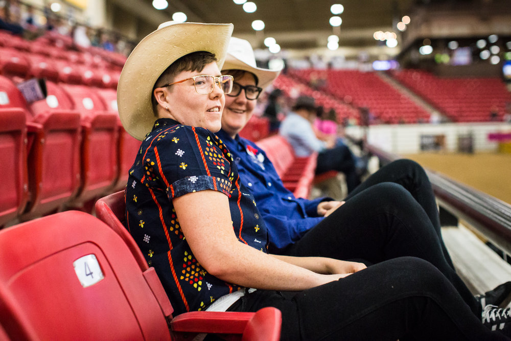 "Amanda Kirkhuff and Clyde Petersen watch the Pole Bending event at the World Gay Rodeo Finals in Las Vegas, NV. Amanda grew up going to rodeos, but enjoys the open environment of gay rodeos. ""You always see gay people at rodeos, but it's just unspoken, it's a homophobic space. The gender division is so much better here - the competitors are pretty evenly split."""