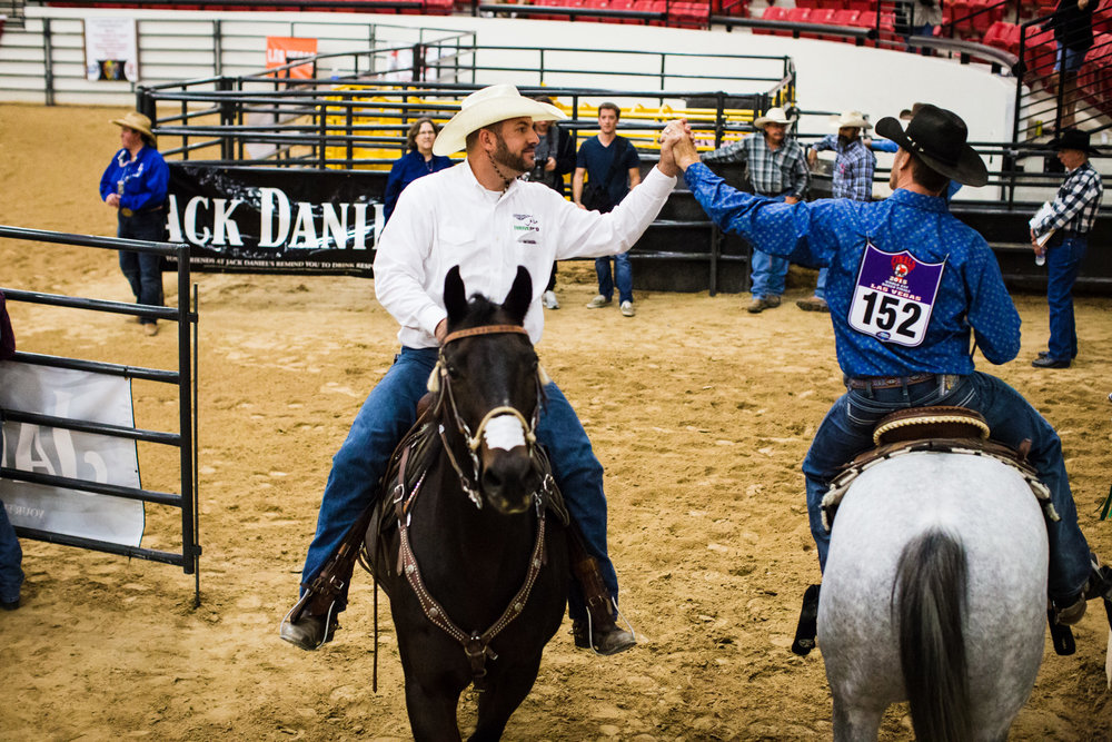 Two contestants congratulate each other during the Mounted Breakaway Roping, in which one team member must rope a steer around the head, and the other must rope one of its back legs, while riding a horse.