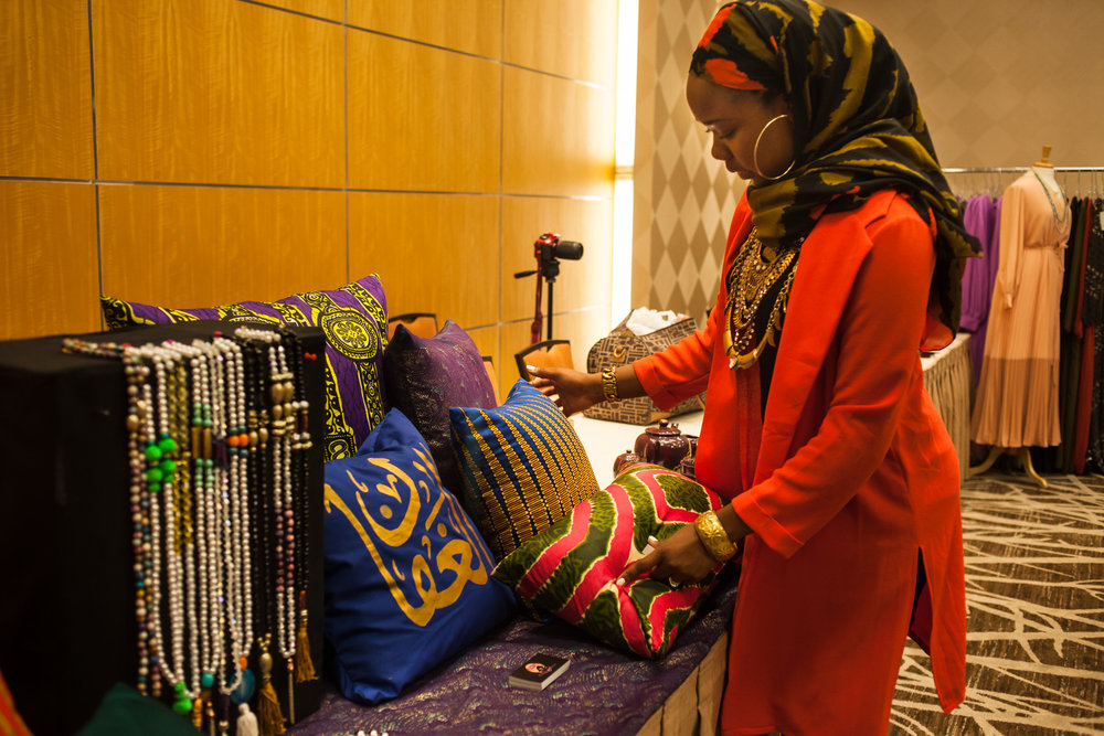 Hakeemah Cummings arranges decorative pillows for sale at a fashion show hosted by Reaching All HIV+ Muslims in America (RAHMA) in Washington, DC on Aug. 16, 2014.