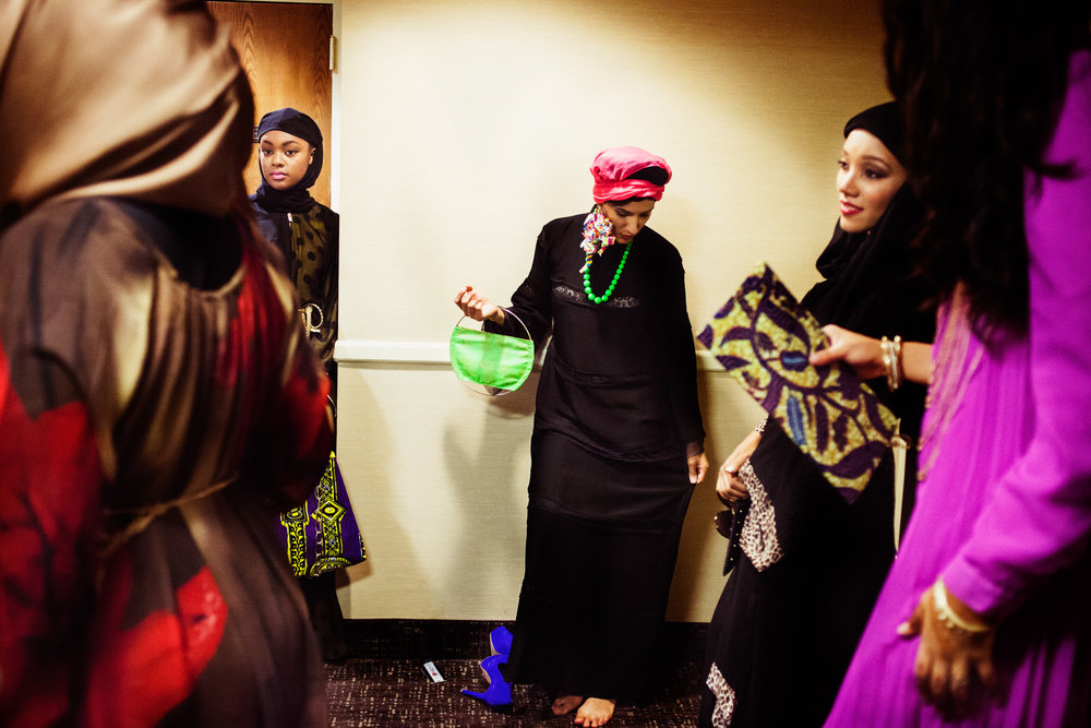 Lilly Matini (center) takes off her blue high heels to rest before heading to the catwalk. Reaching All HIV+ Muslims in America (RAHMA) hosted a fashion show in Washington, DC on Aug. 16, 2014.