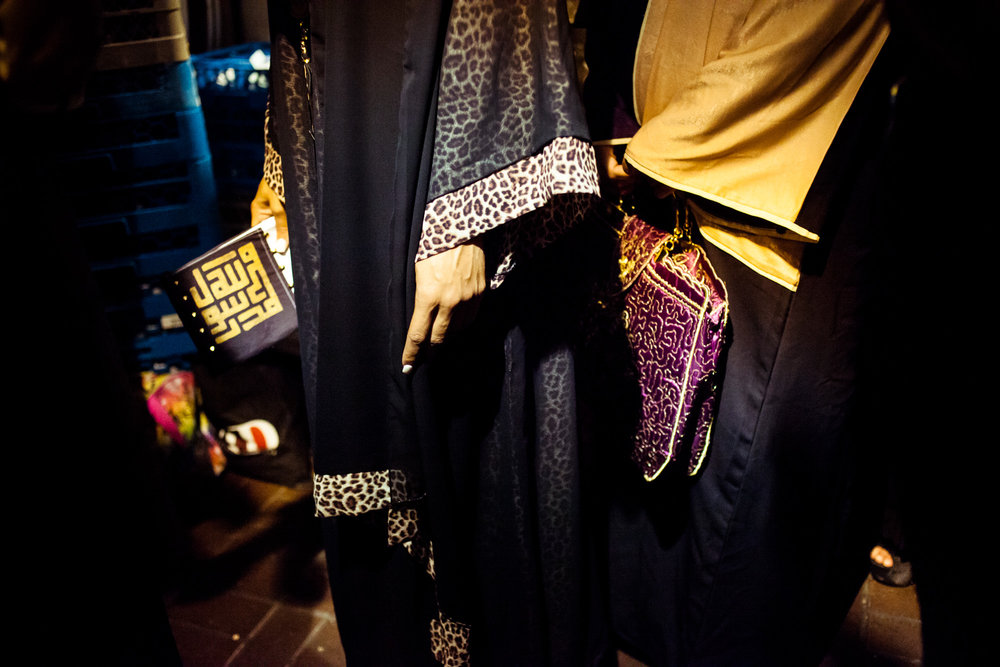Models wearing abayas and holding purses decorated with Arabic calligraphy wait backstage. Reaching All HIV+ Muslims in America (RAHMA) hosted a fashion show in Washington, DC on Aug. 16, 2014.