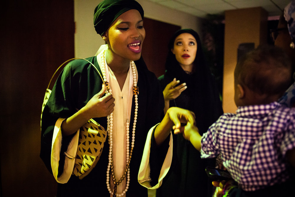 A model greets a young boy after walking the catwalk at the RAHMA fashion show in Washington, DC.