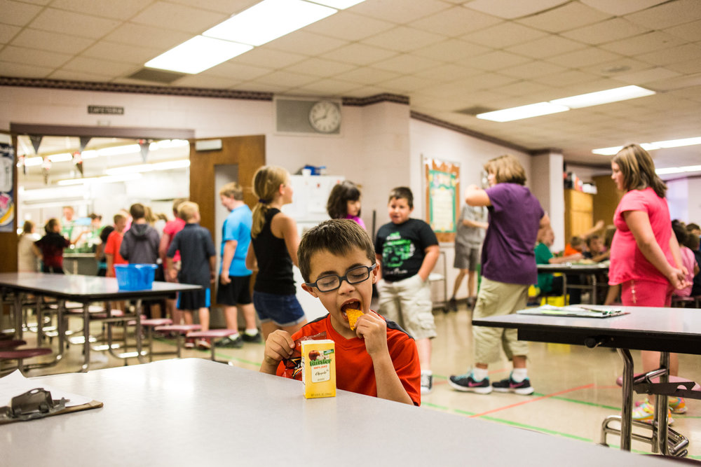 Treven starts eating his lunch he brought from home while his classmates stand in line at the cafeteria.