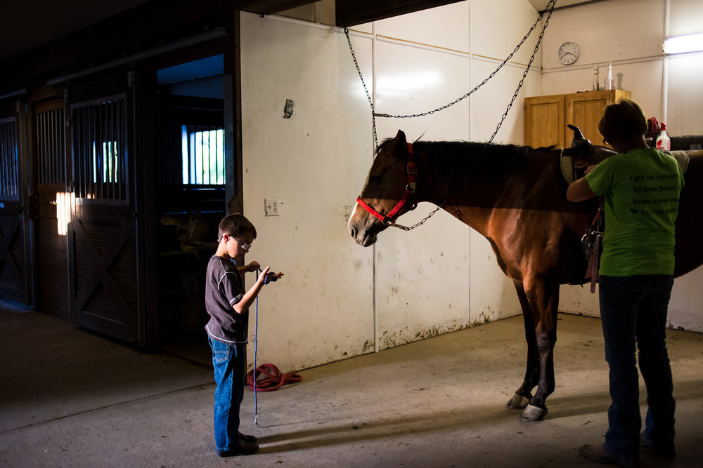 Treven's instructor, Krystal, shows him how to take care of the horse after his therapy session. The therapy is meant to help Treven develop his motor skills, build muscle strength, and deal with sensory issues that come with being around animals and people.