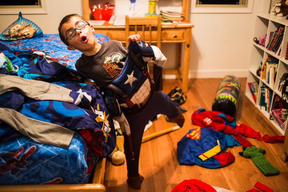 Treven tries on one of his many superhero costumes in his bedroom. Like other kids his age, he loves cartoons and superhero movies.
