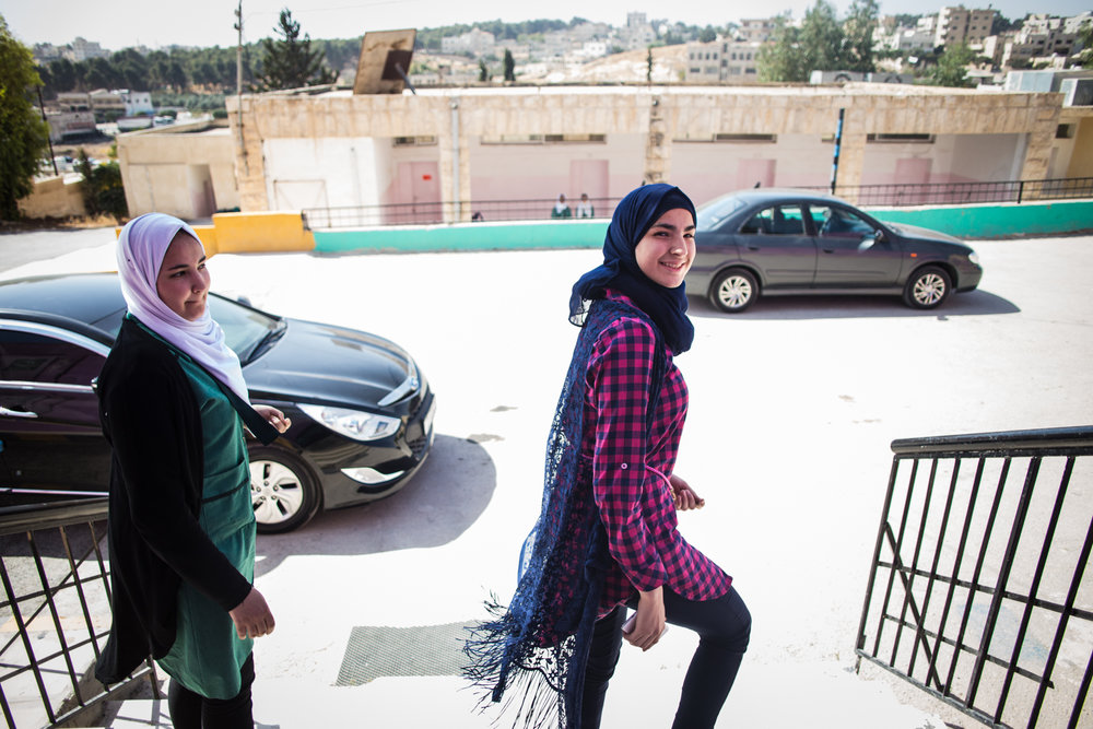 Rand picks up her younger sister (left) from their school south of Amman. Between her studies, football practice, religious devotion, and duties helping her younger siblings, Rand has a full schedule.