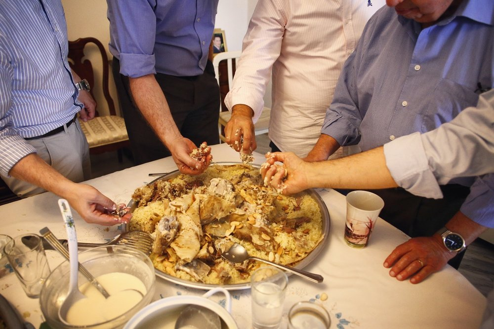 My husband's relatives gather around to eat Mansaf, the traditional Jordanian dish, during Eid al-Fitr after Ramadan, 2016.