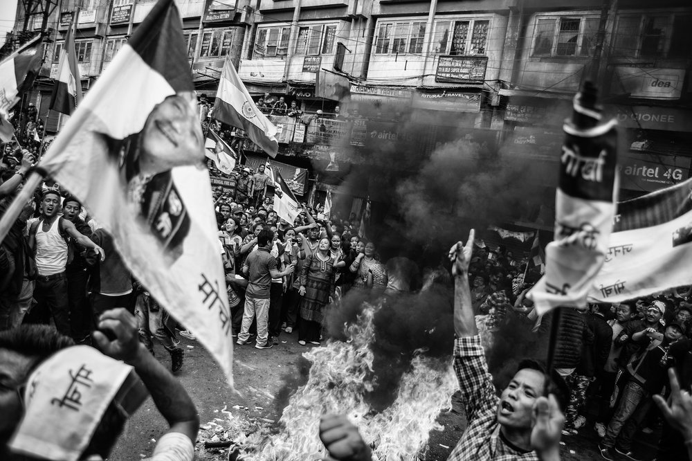 Protesters cheer as they burn copies of the Gorkha Territorial Administration Act and agreement on June 27 at Chowk Bazaar in Darjeeling.