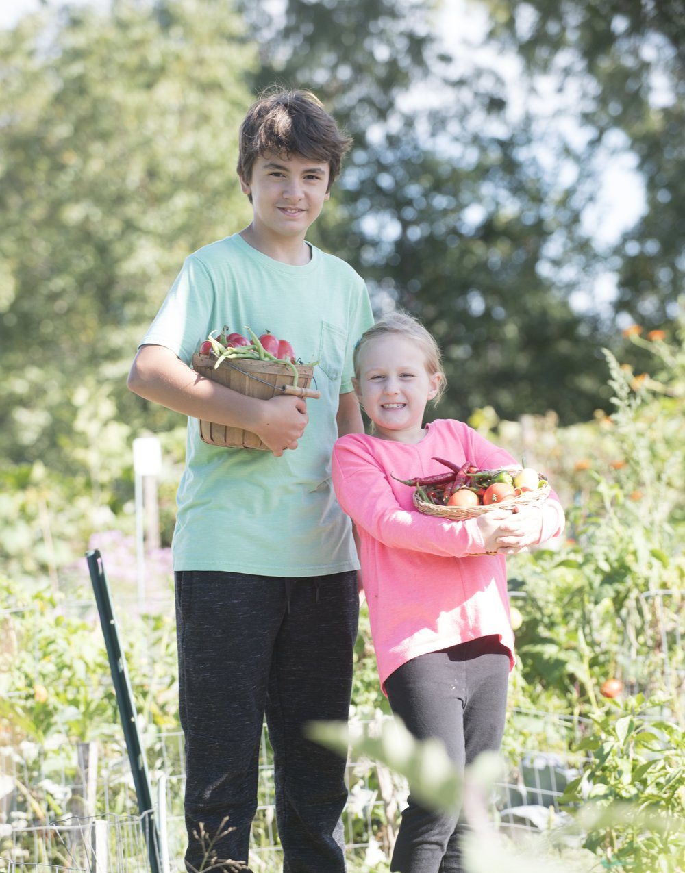 Girl and boy in garden with vegetable baskets.jpg