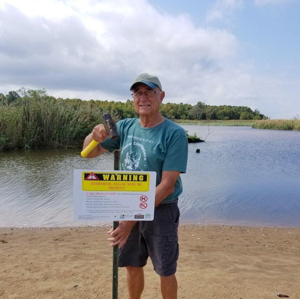Sassafras Riverkeeper Emmett Duke posts a sign warning of harmful algae at the tidal pond between Turners Creek and Llyod Creek.