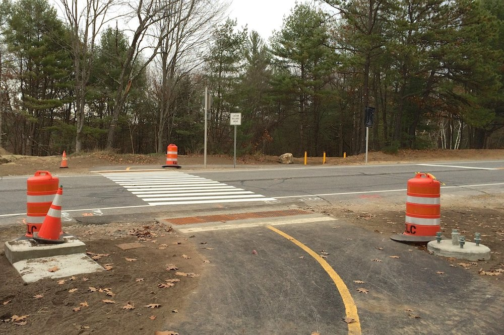 Painted road markings and light pole bases at eastern Mast Road crossing