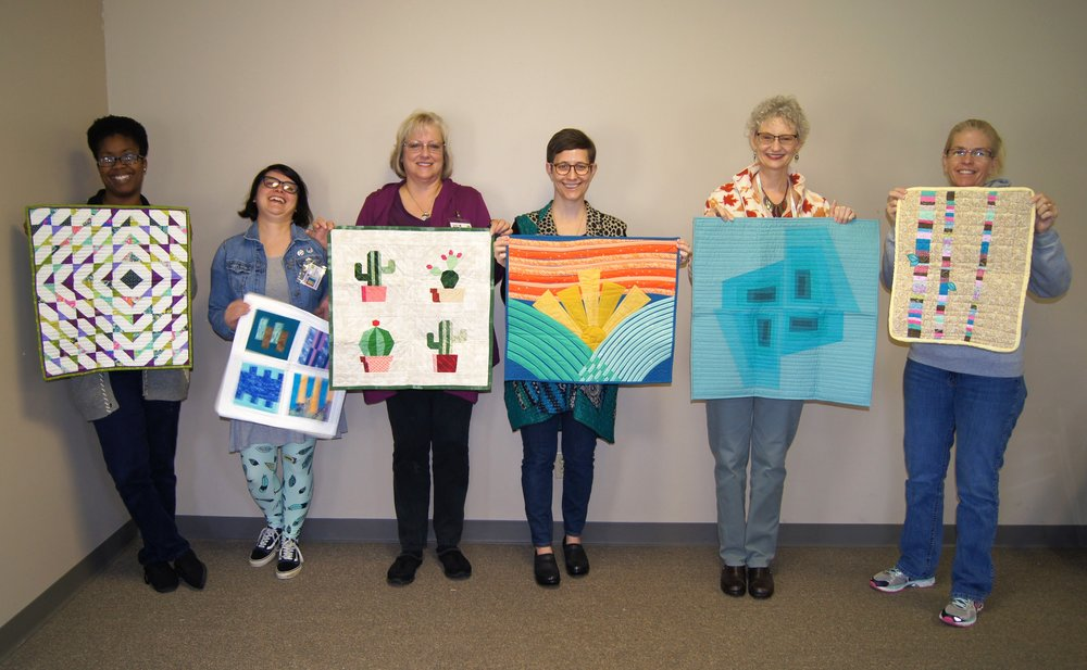 Camille, Samantha, Karen D., Kelly, Denise and Sara show off the mini quilts they received from their swap partners.