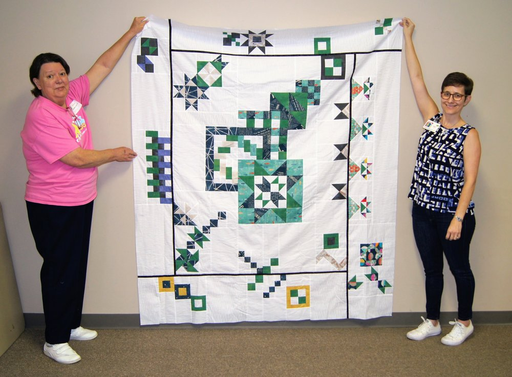Beverly (left) made this Modern Meander mystery quilt top from a Debbie Caffrey pattern