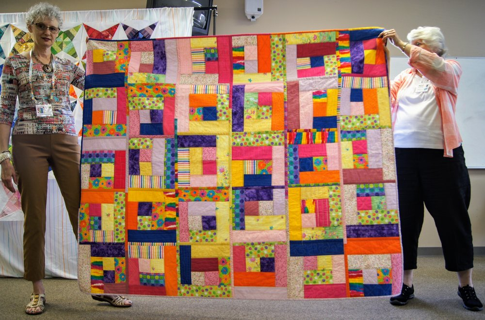 Denise (left) and her colorful quilt-as-you-go work
