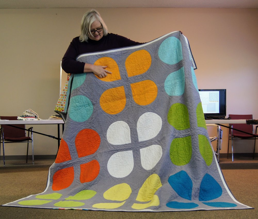 Janet Suber points to words she included in the machine quilting to commemorate the first QuiltCon.
