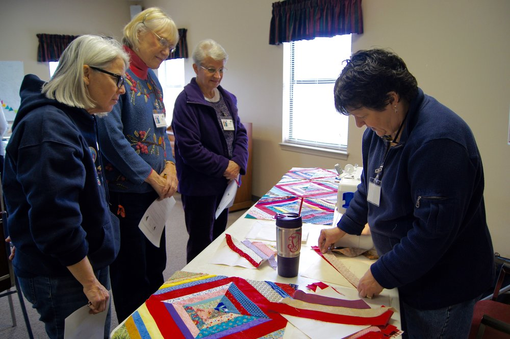Toni Faidley shows members how to paper piece strips
