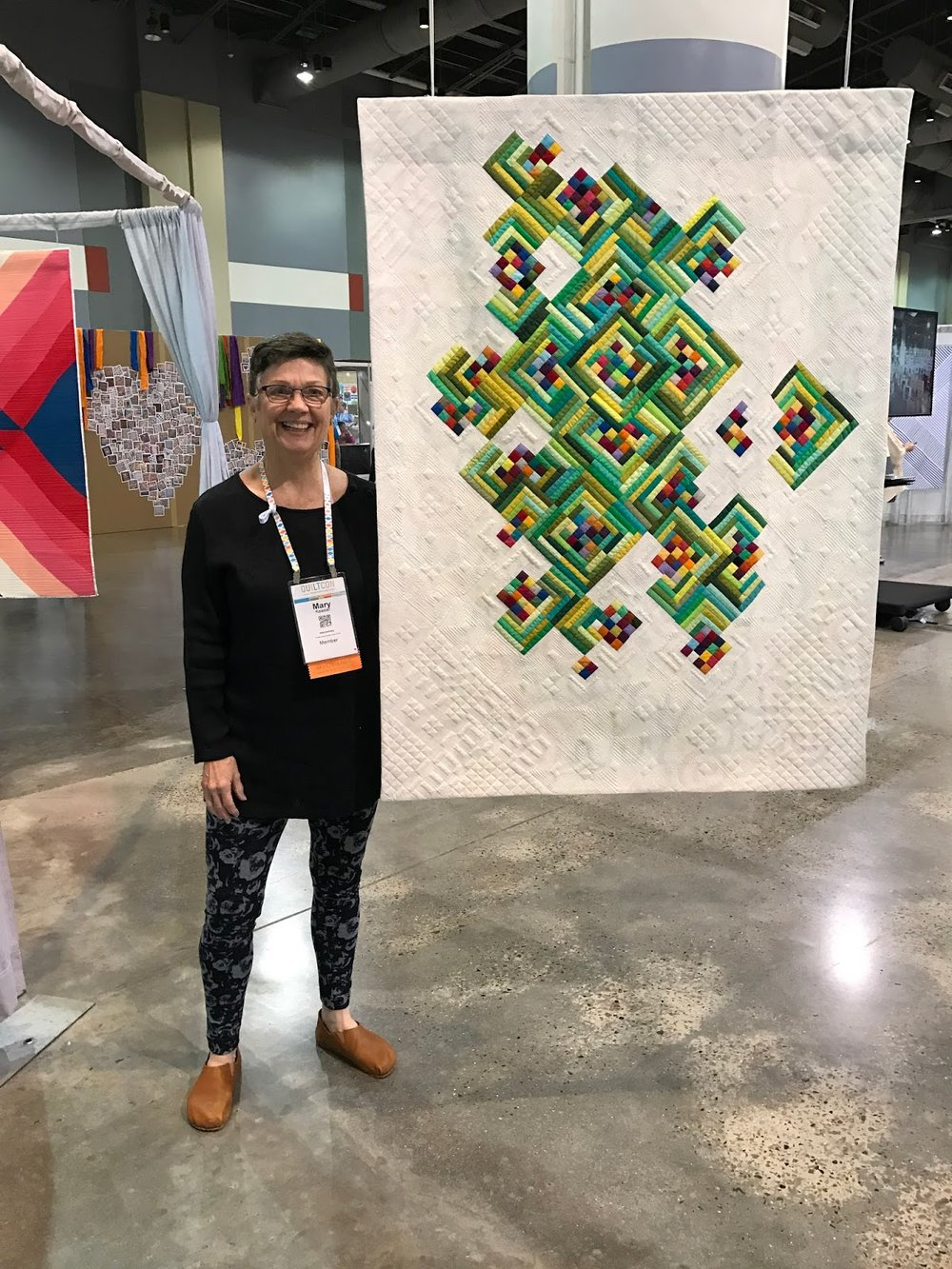 "Mary Keasler and her award-winning quilt ""Not Easy Being Green"""