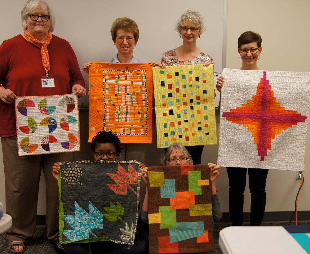 ChattMQG members show the quilts they made for the Tennessee Modern Mini Quilt Swap.