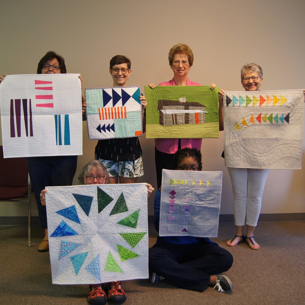 ChattMQG members show the quilts they received in the Tennessee Modern Mini Quilt Swap.