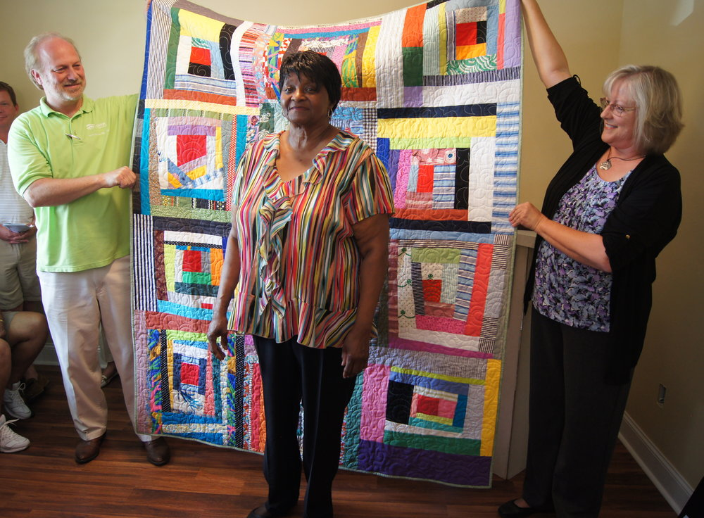 Karen Downer (right) presents a quilt to Alice Smith (center).Photo courtesy of Habitat of Humanity of Greater Chattanooga.