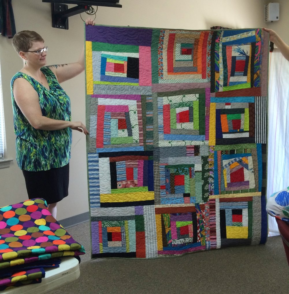 The log cabin blocks in this quilt were made with donated fabric.