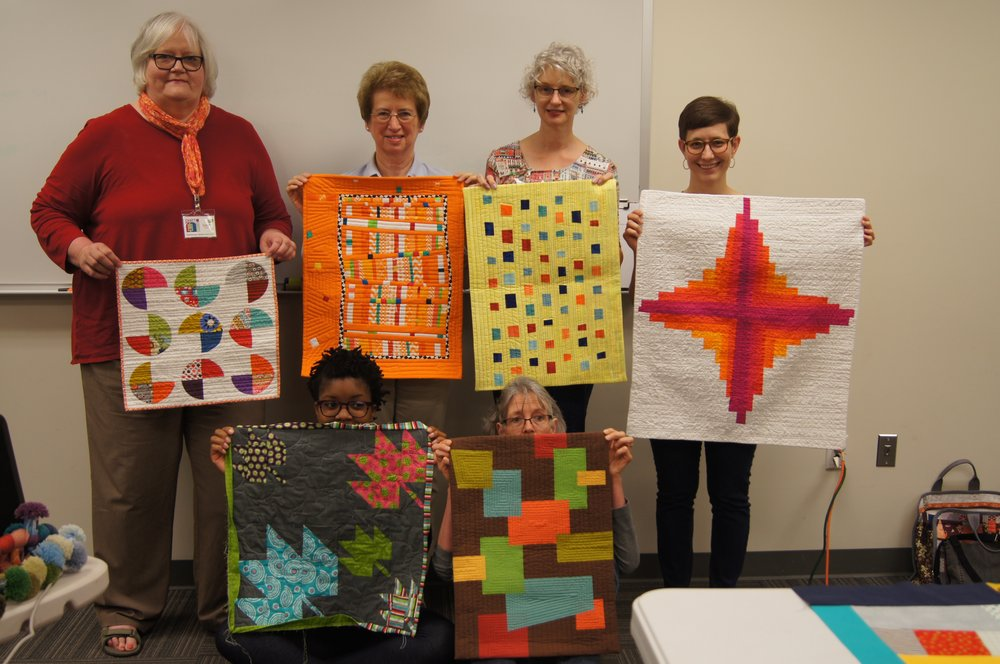 Janet, Theresa, Denise, Kelly, Camille and Audrey show off the quilts they made for their swap partners.