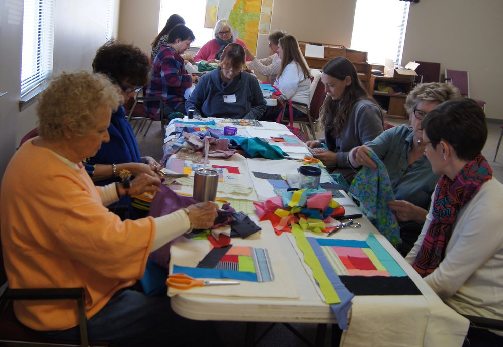 Members make log cabin blocks using donated fabric