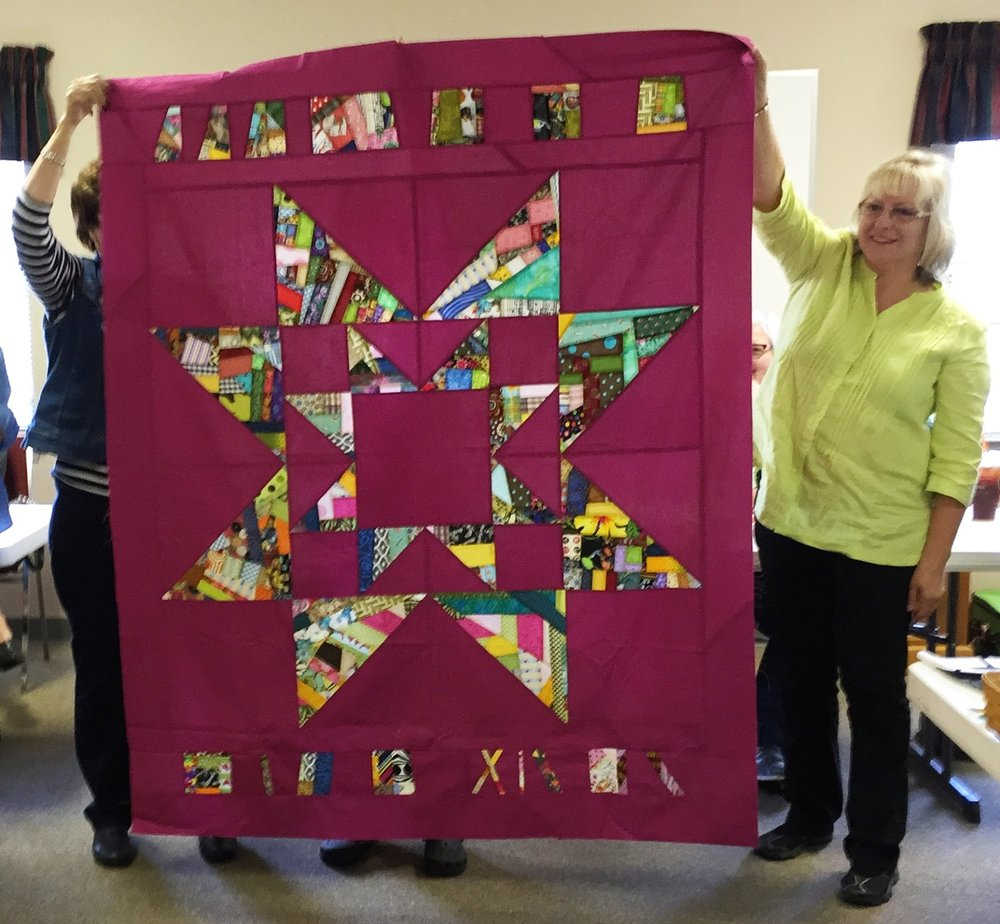 Karen (right) helps hold Team Jean's quilt top