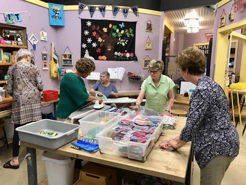 SEW FUN! ChattMQG members Denise Ohlman, Sandi Suggs, Ann Hurley and Theresa Kitchell work with Museum Experience Manager Karen Dewhirst to assemble pillowcase kits.