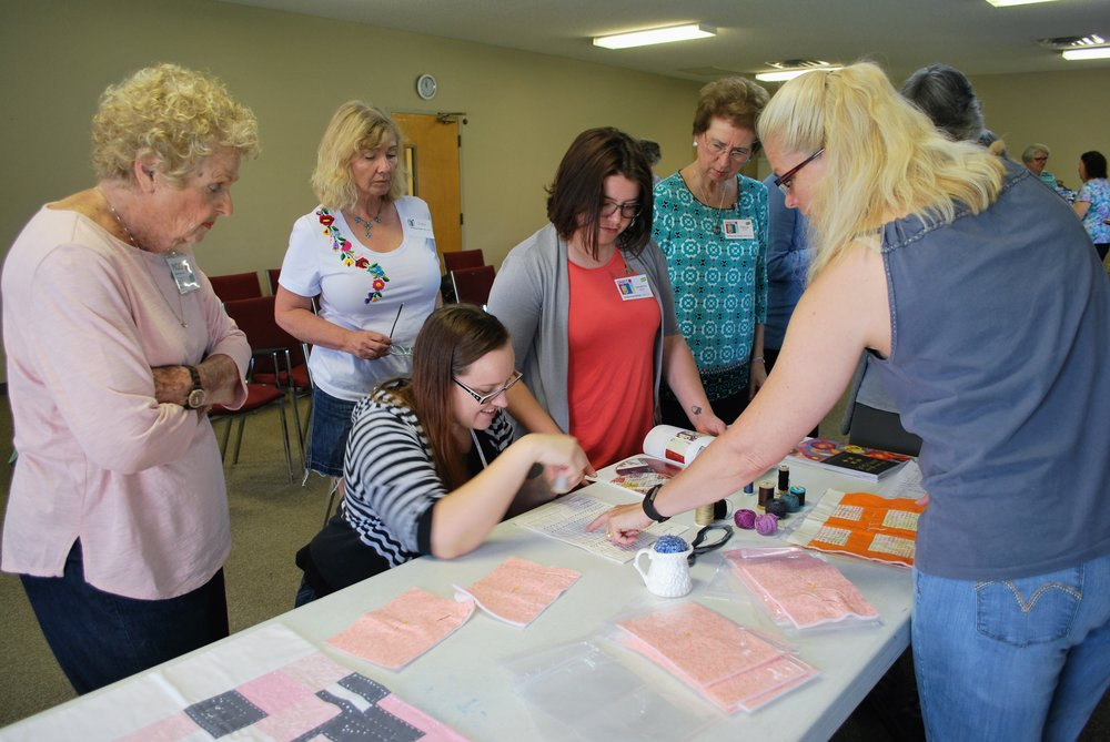 Sara Bradshaw (right) gives ChattMQG members tips for successful utility stitching.