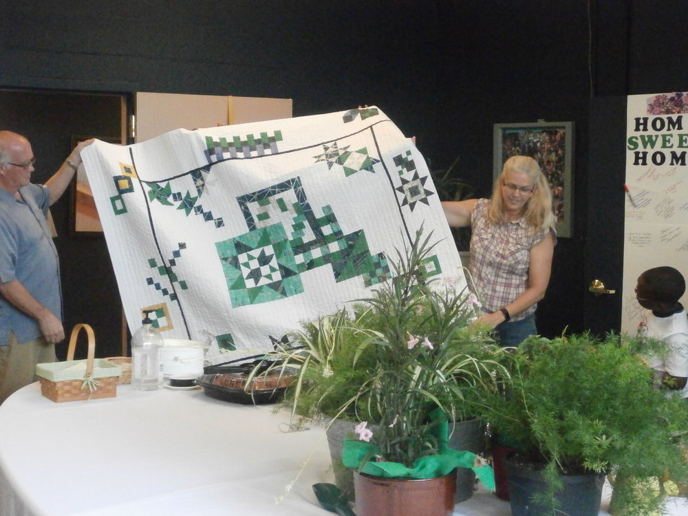 Sara (right) presents the quilt