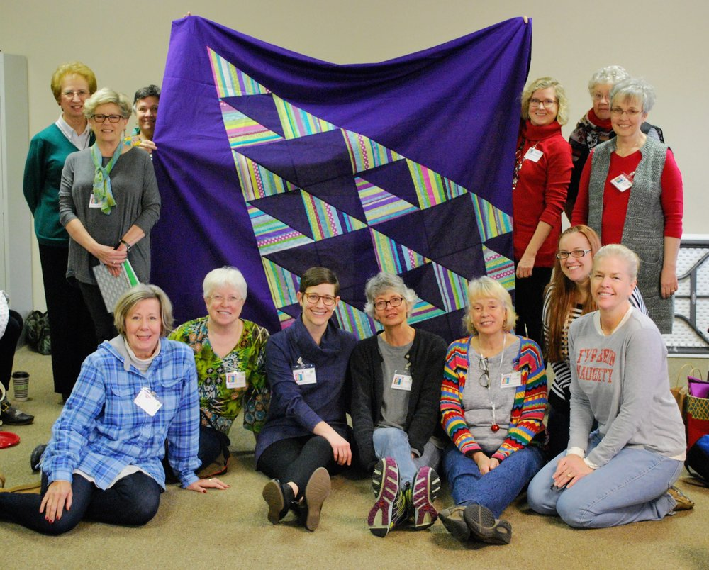 Members who stitched portions of the quilt include Theresa, Ann, Mary, Pat, Martha S., Kelly, Audrey, Donna, Leslie, Helen, Patricia, Stephanie, and Sara. Thanks to everyone in the guild who helped!