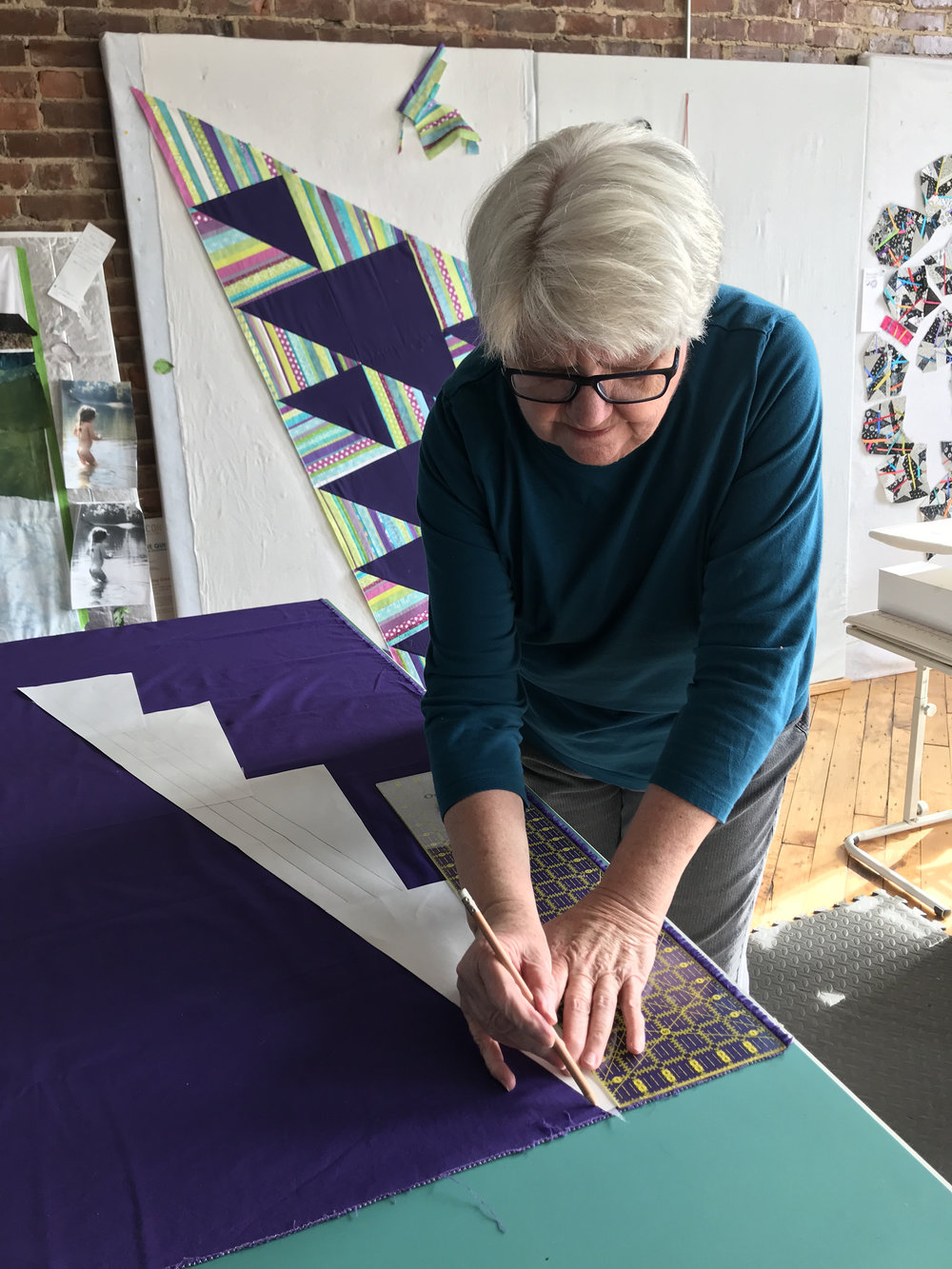 Jean determines how to cut the background fabric to keep it on grain.