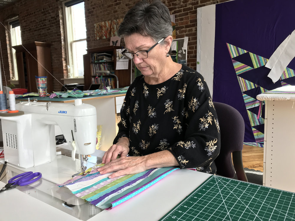 Mary sews strips to create the handle.