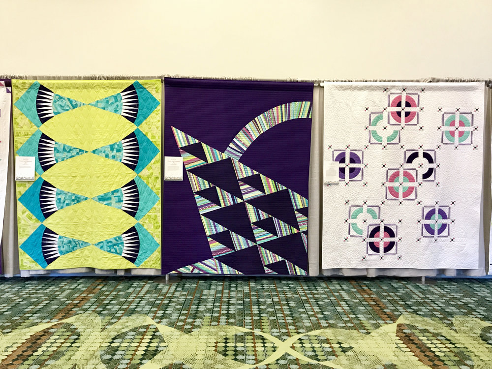 Our modern basket quilt (center) hangs at QuiltCon between quilts made by Knoxville MQG (left) and Music City MQG (right).
