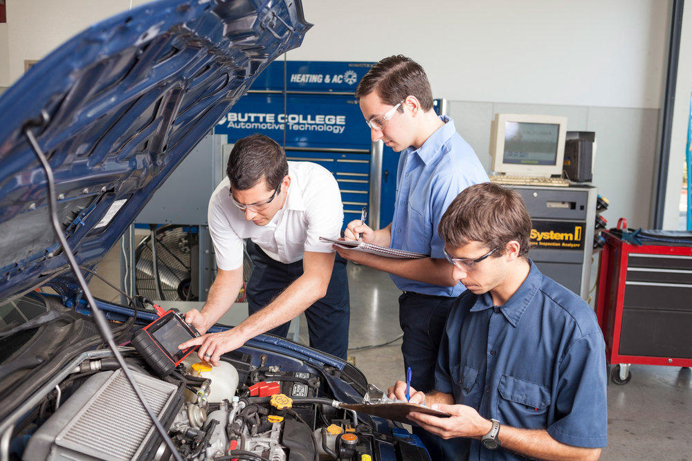 A student smog technician is instructed at a computer station in an automotive repair shop.